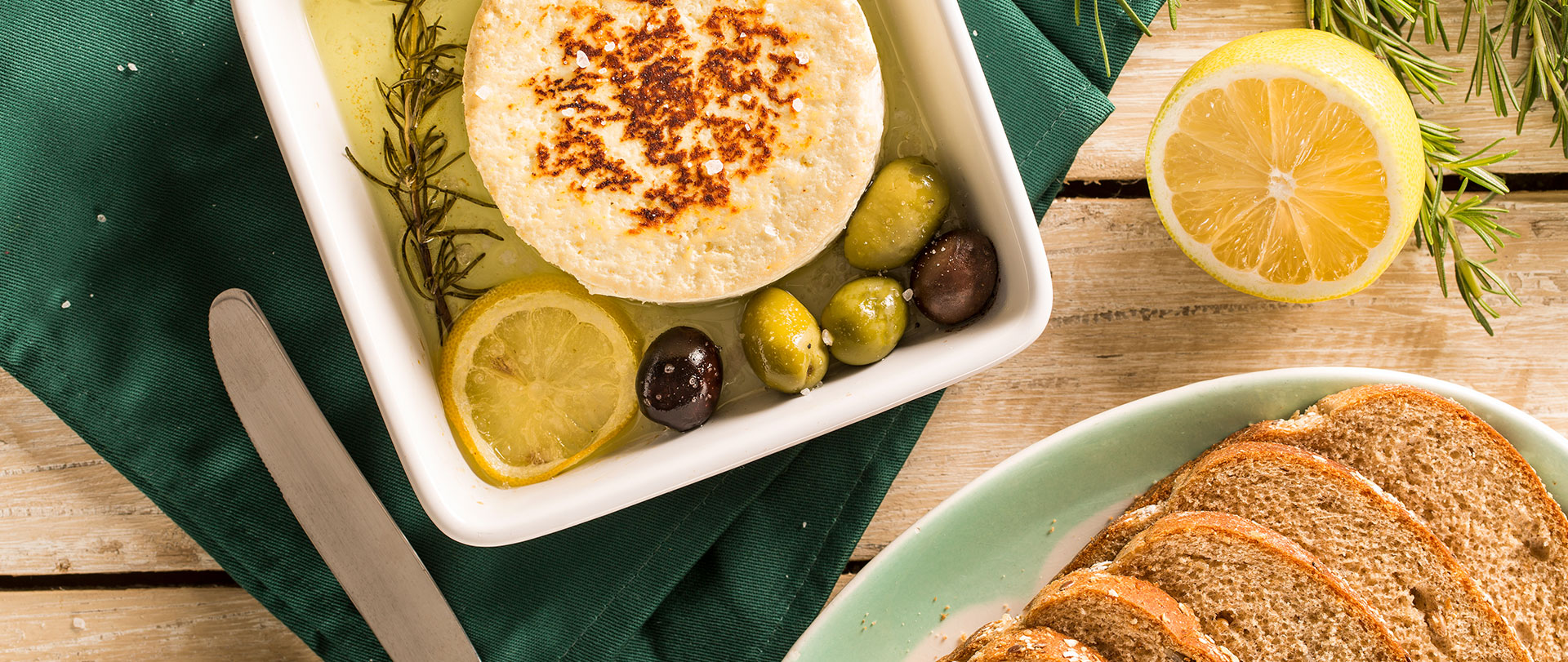 Queijo com azeite, azeitonas e limão, servido com pão integral