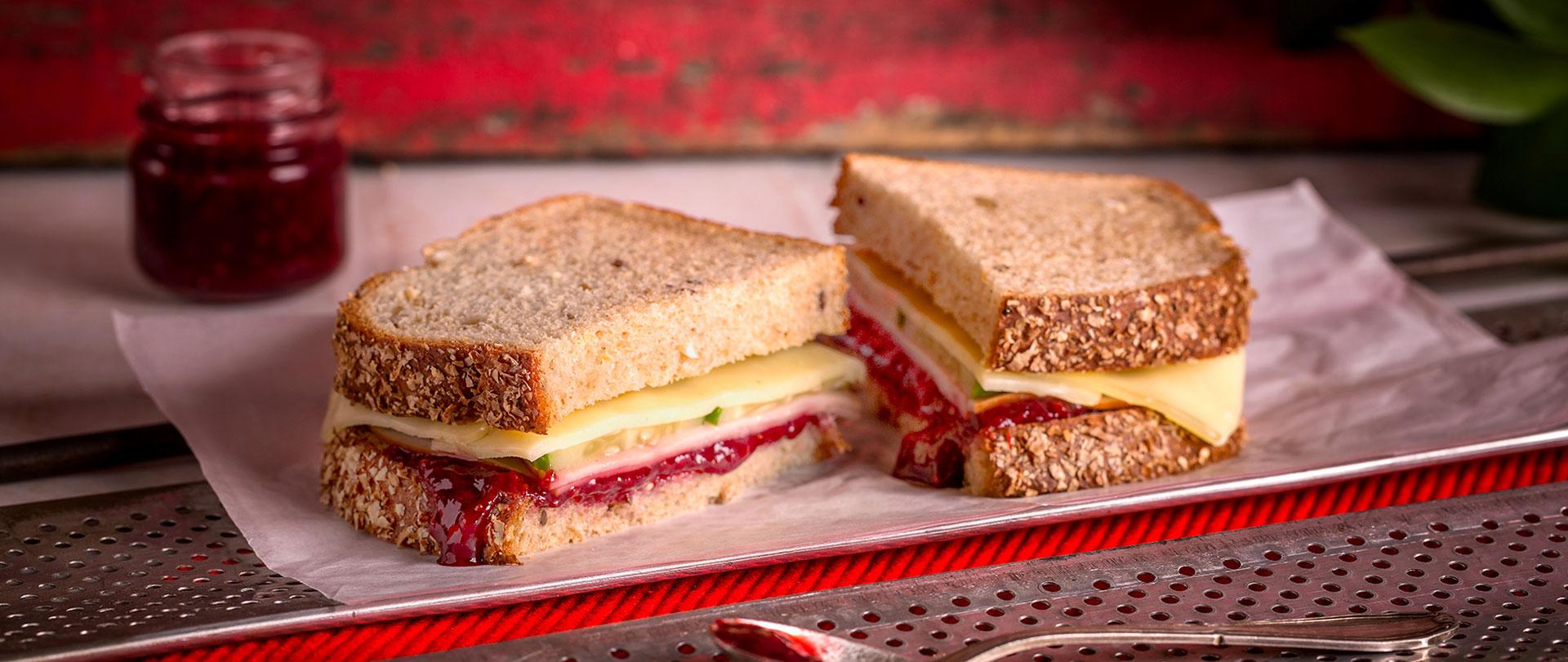 Sanduíche agridoce com geléia de morango, peito de peru, pepino