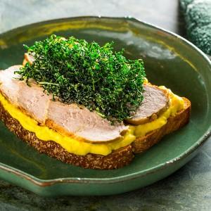 Sanduíche aberto de pernil, pasta de curry e couve crispy
