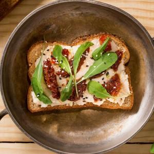 Sanduíche aberto de feijão branco, tomates secos e rúcula